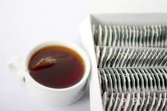 Té en taza y bolsitas de té en caja Imagen de archivo libre de regalías