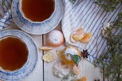 Té en tazas hermosas de la porcelana Mañana del ` s del Año Nuevo Mandarines y tazas de té en un fondo de madera blanco Visión su Fotografía de archivo libre de regalías