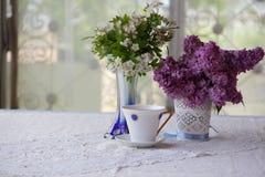 Té en una taza hermosa y un ramo de ramas de un blossomi Foto de archivo libre de regalías