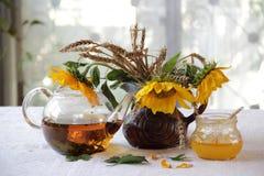 Té en una tetera transparente, miel y un ramo de girasoles Fotos de archivo libres de regalías
