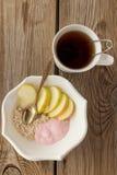Té, harina de avena, manzanas y yogur Foto de archivo