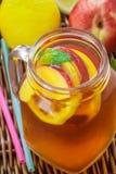 Té helado con el limón y el melocotón en un tarro de albañil Refresco del verano Foto de archivo