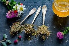 Té, infusión de hierbas, flores y miel secos imagen de archivo