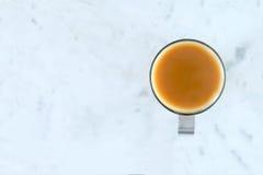 Té lechoso en la taza de cristal en la superficie de mármol Imagen de archivo