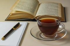 Té, libro y cuaderno en la tabla fotos de archivo libres de regalías