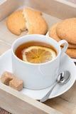 Té negro con el limón y las galletas, verticales Foto de archivo libre de regalías
