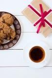 Té negro con las galletas y el regalo en un fondo de madera blanco Imágenes de archivo libres de regalías