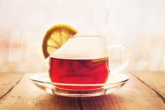 Té negro con las rebanadas del limón en una taza de cristal Foto de archivo