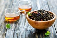 Té negro con los pétalos de la flor en cuenco y tazas de té caliente Fotos de archivo