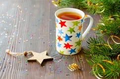 Té negro de la Navidad en taza con las estrellas y la decoración multicoloras de la Navidad Imagenes de archivo