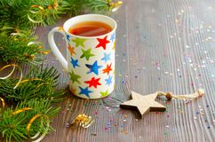 Té negro de la Navidad en taza con las estrellas y la decoración multicoloras de la Navidad Foto de archivo libre de regalías