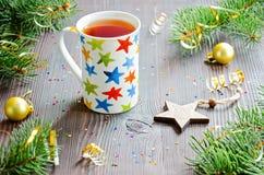 Té negro de la Navidad en taza con las estrellas y la decoración multicoloras de la Navidad Fotos de archivo libres de regalías