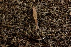 Té negro en una cuchara del metal en un fondo del té negro Foto de archivo