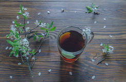 Té negro en una rama de la taza y de la cereza que miente en superficie de madera Color del vintage Foco selectivo Fotografía de archivo