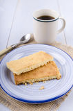 Té negro en una taza y una placa con la torta dulce escocesa Fotografía de archivo libre de regalías