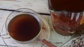 Té negro, exprimidor manual con los limones Un jarro de té negro y cubos del azúcar almacen de metraje de vídeo