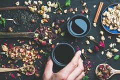 Té negro y cucharas chinos con las hierbas y los brotes de flor Imagen de archivo libre de regalías