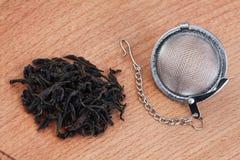 Té negro, y tamiz del té con la cadena, en fondo de madera imagen de archivo