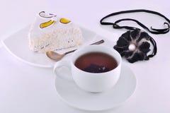 té negro y una rebanada de torta en una placa Foto de archivo libre de regalías