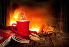 Té o café caliente en una taza, un libro y una chimenea rojos Imagenes de archivo