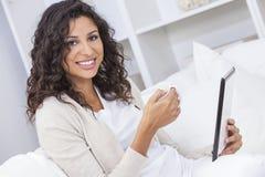 Té o café de consumición de la mujer usando la tableta foto de archivo libre de regalías