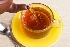 Té que es vertido en la taza de té con el platillo Imagenes de archivo
