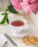 Té rojo de la baya o de la fruta en taza de té con la peonía Foto de archivo