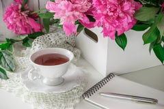 Té rojo de la baya o de la fruta en taza de té con la peonía Imagenes de archivo