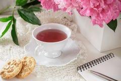 Té rojo de la baya o de la fruta en taza de té con la peonía Fotografía de archivo libre de regalías