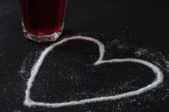Té rojo de las bayas en el vidrio, azúcar derramado en la forma del corazón imagenes de archivo