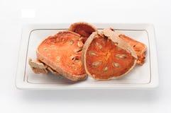 Té seco de la fruta de Bael (marmelos de Aegle) aislado en plato y b blanco Imagen de archivo libre de regalías