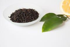 Té seco en un cuenco y un limón hermosos con las hojas verdes Fotos de archivo