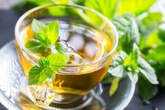 Té Té de la menta Té herbario Hoja de la menta Hojas de menta El té en una taza de cristal, hojas de menta, secó el té, cal corta foto de archivo libre de regalías