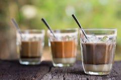 Té tailandés de la leche de la bebida caliente, café sólo, bebida local de la calle de la firma del cacao en la tabla de madera Imágenes de archivo libres de regalías