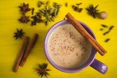 Té tradicional de la leche con las especias en una tabla amarilla Foto de archivo
