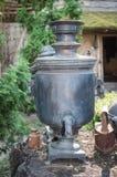 Té tradicional ruso viejo - samovar de consumición Imagenes de archivo