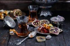 Té turco con las tazas de cristal auténticas Dos tazas de té turco y dulces en fondo de madera oscuro Foto de archivo libre de regalías