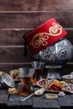 Té turco con las tazas de cristal auténticas Dos tazas de té turco y dulces en fondo de madera oscuro Foto de archivo