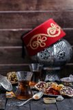 Té turco con las tazas de cristal auténticas Dos tazas de té turco y dulces en fondo de madera oscuro Imágenes de archivo libres de regalías