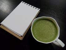 té verde caliente con la página en blanco del cuaderno abierto Imagen de archivo libre de regalías