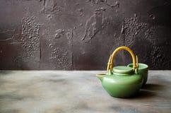 Té verde chino en tetera en fondo oscuro Foto de archivo