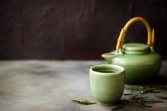 Té verde chino en tetera en fondo oscuro Imagen de archivo