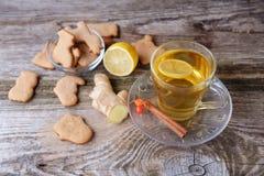 Té verde con el limón, galletas del jengibre en los pequeños animales en la tabla Foto de archivo libre de regalías