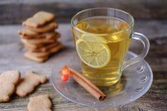 Té verde con el limón, galletas del jengibre en los pequeños animales en la tabla Imagen de archivo