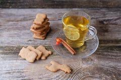 Té verde con el limón, galletas del jengibre en los pequeños animales en la tabla Fotografía de archivo libre de regalías