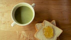 Té verde con la rebanada de los panes con el atasco anaranjado Foto de archivo libre de regalías