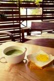 Té verde con la rebanada de los panes con el atasco anaranjado Fotos de archivo