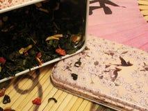 Té verde de la fruta en estaño y ventilador chino Imagen de archivo