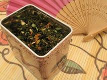 Té verde de la fruta en estaño y ventilador chino Fotografía de archivo libre de regalías
