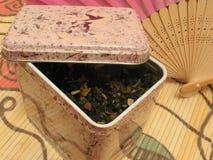 Té verde de la fruta en estaño y ventilador chino Fotos de archivo